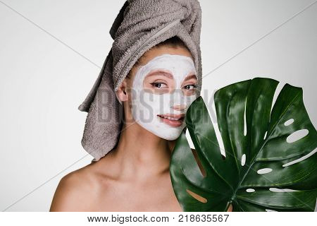 smiling girl looks after her face, has applied a nutritious white mask on her face, on her head a towel
