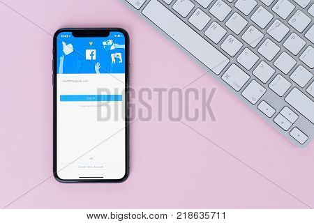WARSAW, POLAND - DECEMBER 02, 2017: New Iphone X mobile phone with facebook page on pink background