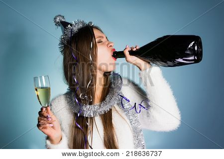 funny drunk girl celebrates the new year 2018, corporate, drinks champagne from a bottle