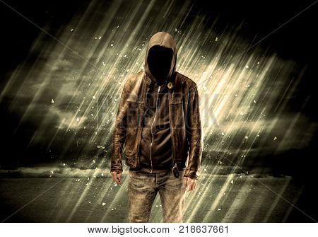 An incognito hooded stalker standing in the rain with his back in front of dark scary landscape concept poster