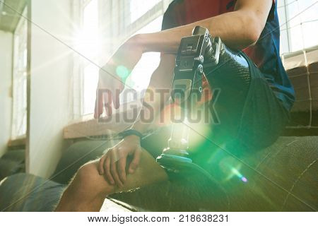 Close up of amputee sportsman sitting on bench in modern gym, focus on prosthetic leg in sunlight with lens flare