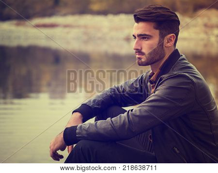 Handsome young man on a lake's shore at dusk of a sunny, peaceful day, sitting