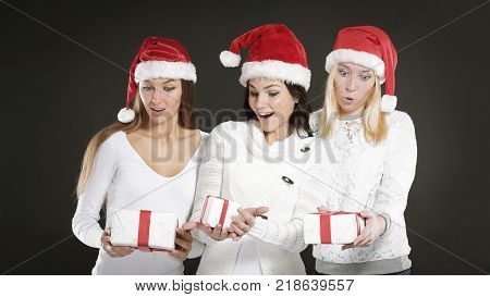 three happy young women in costume of Santa Claus with Christmas gifts.photo with copy space.