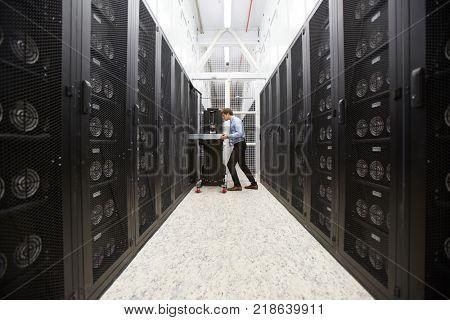 Staff of bitcoin storage system service examining hardware in mining farm