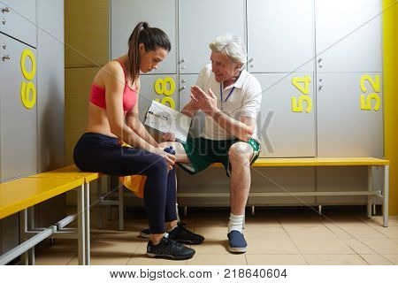 Upset girl in sportswear listening to her disappointed trainer after the last game