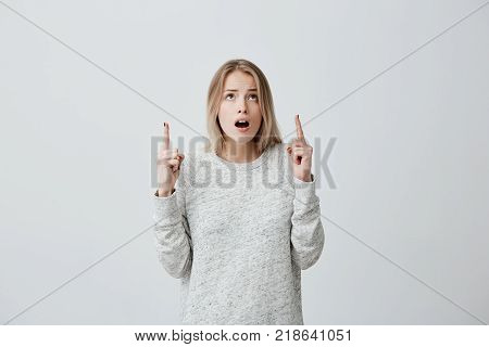 Astonished female with blonde dyed hair, in sweater looking and pointing upwards with her fingers being surprised to see something. Concerned excited young woman with wide opened mouth