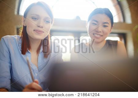 Young businesswoman and her colleague looking through curious information in the net while sitting in cafe