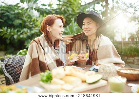 Two intercultural girlfriends wrapped in plaid sitting by table and having drinks