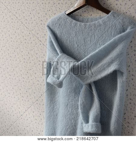 Pastel blue knitted woolen sweater on a hanger