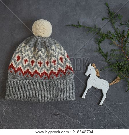 Gray winter hat with a jacquard pattern on a gray background with a wooden horse closeup.