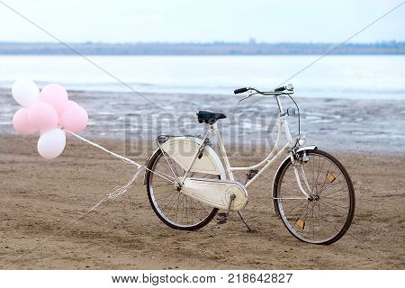 Retro bike on the beach with pink balloons