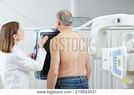 Young professional radiologist talking to senior patient standing close to x-ray screen