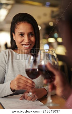 Successful co-workers clinking by glasses with red wine after discussion of contract terms
