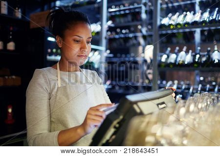 Pretty young cashier registrating orders of clients of cafe, bar or restaurant