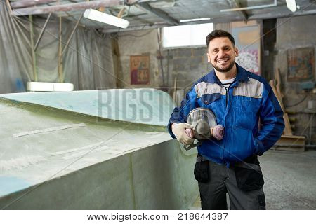 Portrait of modern mature man smiling at camera while posing in yacht workshop next to repaired boat and holding respirator, copy space