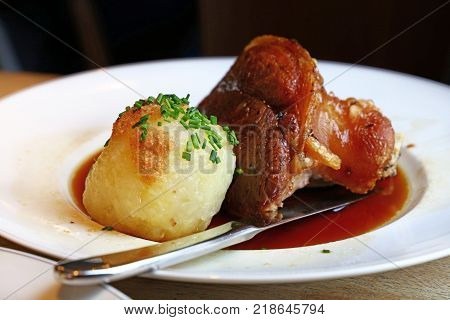 Portion of roasted succulent pork fore shank or knuckle with Bavarian dumplings and chive in plate on table close up low angle view