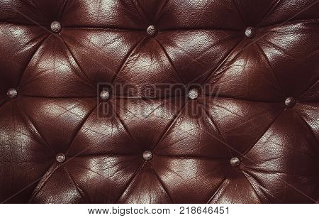 Texture of genuine leather upholstered furniture. Decorative brown background. Decorative background of genuine leather capitone texture