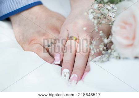 The hands of the newlyweds with wedding rings next to the wedding bouquet. Preparation for cerimony. Organization of weddings. Floristics. Manicure.