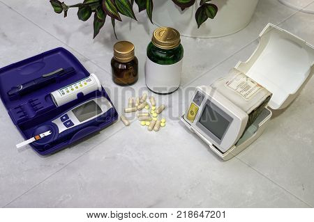 On the table are medical devices. Blood pressure meter blood sugar level meter and tablets. Everything for home use.