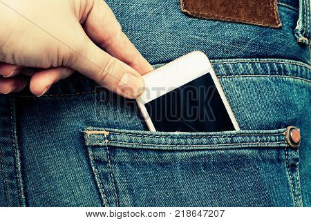 The hand pulls the phone out of the jeans pocket. Theft on vacation.