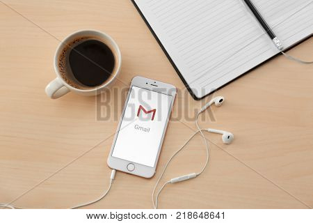 KIEV, UKRAINE - OCTOBER 12, 2017: Modern iPhone SE Rose Gold with Gmail app on screen, cup of coffee and earphones on wooden table