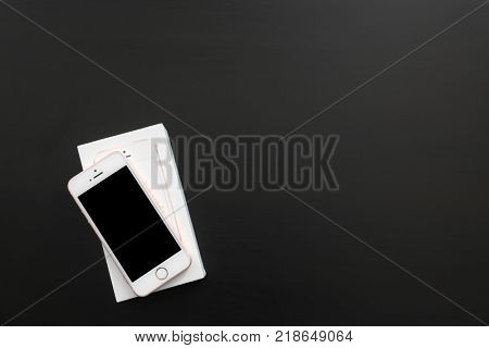 KIEV, UKRAINE - OCTOBER 17, 2017: Rose Gold iPhone SE and box on black table