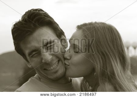 Portrait Of A Young Couple. Girl Kisses Her Boyfriend And He Makes A Wry Face