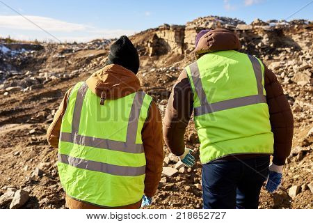 Back view portrait of two industrial workers wearing reflective jackets, one of them African, inspecting mineral mines on worksite outdoors