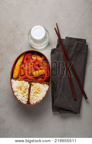 Wooden lunch boxe with healthy food ready to go for work or school, ahead meal preparation or dieting concept. On a old stone table with rust. Top view.