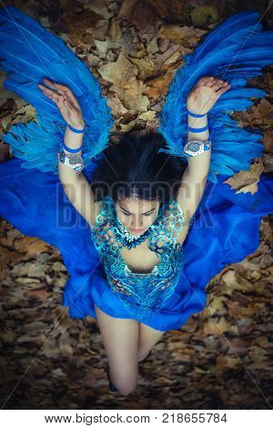Fairy, Gothic beautiful brunette girl in a suit made of blue wires, bears bird wings and colorful feathers helmet