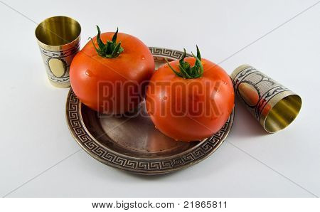Tomato on a silver plate with two cups