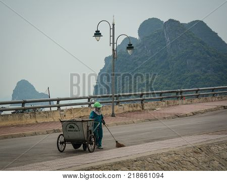 Ha Long Vietnam - May 23 2016. A woman cleaning street in Ha Long Vietnam. Ha Long a city on Vietnam northern coast is a jumping-off point for Ha Long Bay.