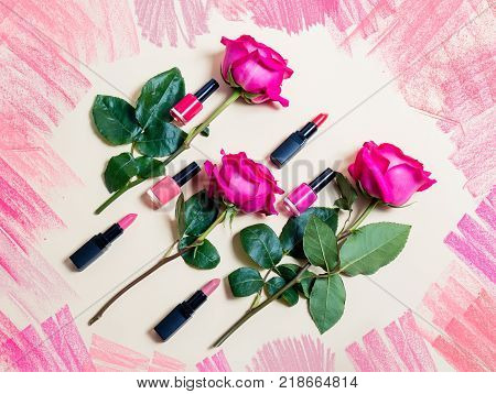 Colorful lipsticks nail polishes and roses on beige background