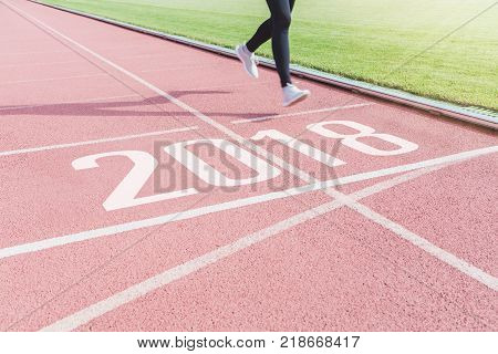 Female athletes are running into the finish line at number 2018. In the running track of the stadium.Concept of new year 2018 business goal.