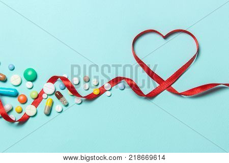 Tablets to treat the heart from a heart attack. Red ribbon in the form of heart and cardiogram