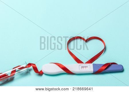 Artificial insemination a child from a test tube infertility treatment. Positive pregnancy test with two strips and a red ribbon in the form of a heart and a test-tube