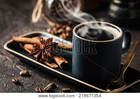 Fresh tasty black espresso cup of hot coffee with cinnamon, anise stars and coffee beans on dark background
