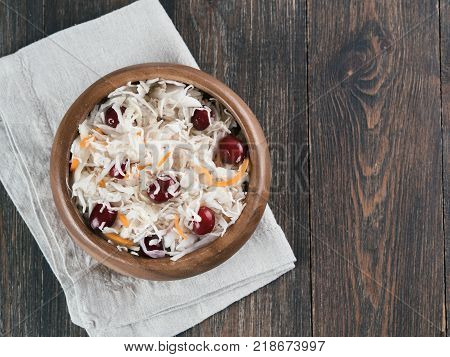 Traditional russian appetizer sauerkraut with cranberry and carrot in wooden bowl on brown rustic wooden table. Fermented cabbage. Russian cuisine and russian kitchen. Top view or flat-lay.