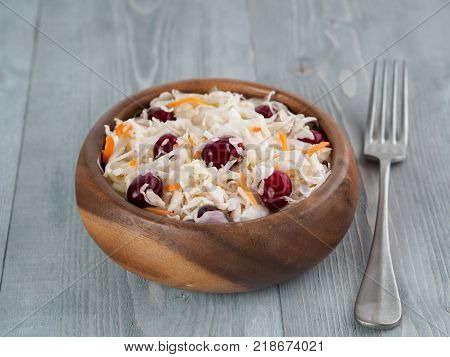 Traditional russian appetizer sauerkraut with cranberry and carrot in wooden bowl on gray rustic wooden table. Fermented cabbage. Russian cuisine and russian kitchen.