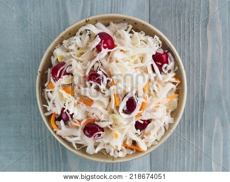 Traditional russian appetizer sauerkraut with cranberry and carrot in craft plate on gray rustic wooden table. Fermented cabbage. Russian cuisine and russian kitchen. Top view or flat-lay.