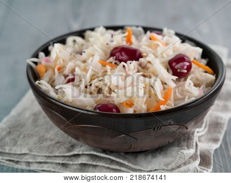 Traditional russian appetizer sauerkraut with cranberry and carrot in dark craft plate on gray rustic wooden table. Fermented cabbage. Russian cuisine and russian kitchen.
