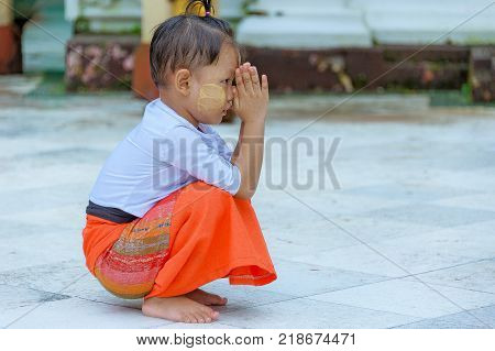 Shwedagon Pagoda, Yangon, Myanmar - Oct 21, 2017: A little Burmese boy kneels down as he clasps his palms and prays to the Lord Buddha.