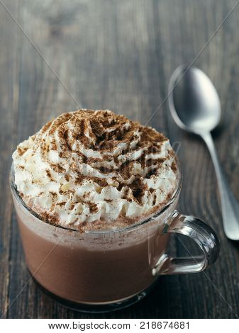 Glass cup with hot chocolate, whipped cream and cinnamon powder.