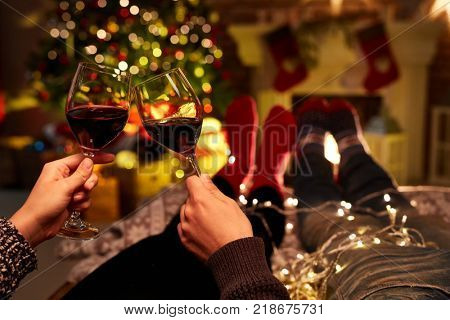Christmas couple at home in Winter. Couple drinking red wine at home in Christmas time. Christmas tree and fireplace in background.