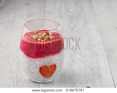 Idea for healthy breakfast on Valentine's Day: Chia pudding with red berry puree, chopped almonds on top and strawberry in the shape of heart. Copy space for text