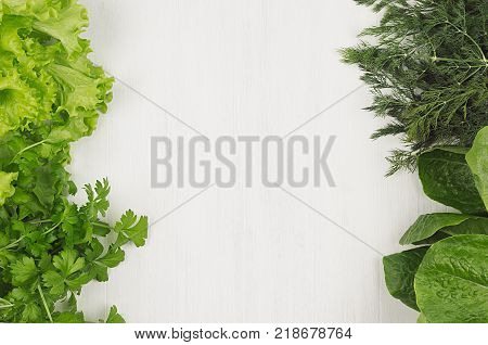 Salad spinach dill parsley sheaves on white wood plank top view decorative border.