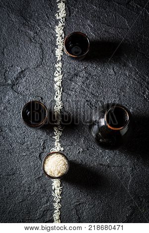 Rice and black ceramics to sake on black rock
