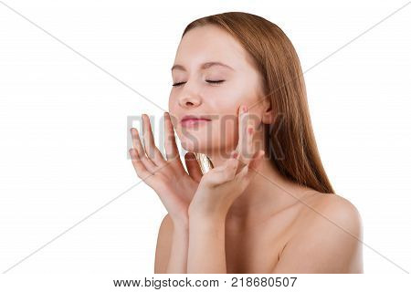 A beautiful young brunette girl, without make-up and with bare shoulders, with her eyes closed, does face massage with her fingertips. Isolated on white background.
