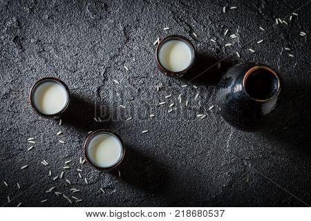 Closeup of white sake in black ceramics on black rock