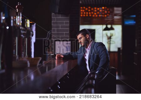 Tired but pleased young cute man in formal attire sits at bar counter with glass of whiskey after long working day